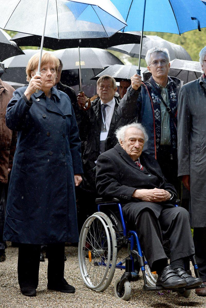 Max Mannheimer (en la silla de ruedas) y la canciller alemana Ángela Merkel (i), durante la ceremonia por el 70 aniversario de la liberación del campo de concentración de Dachau. (Foto Prensa Libre: AP).