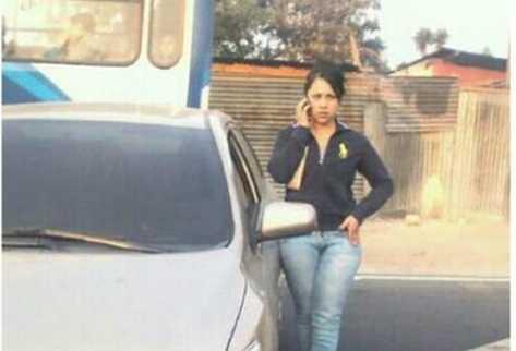 Heidy Véliz, con gesto de molestia, conversa por celular mientras esperan retire su carro.