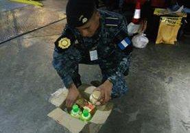 Un agente de la PNC revisa la caja donde se encontró la cocaína, con destino hacia EE. UU. (Foto Prensa Libre: Cortesía)