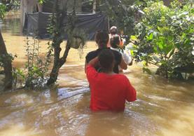 Personas caminan en medio del agua en una aldea de Los Amates, Izabal. (Foto Prensa Libre: Dony Stewart)