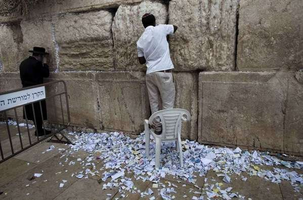 Un empleado quita del Muro de las Lamentaciones los mensajes de ruegos a Dios.