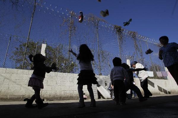 <p>Un grupo de menores lanzan juguetes al aire, frente a una malla perimetral electrificada, en el COF.</p>