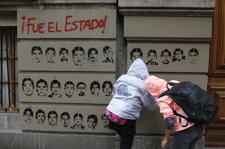 Dos personas pintan los rostros de los estudiantes desaparecidos, durante una manifestación en México. (Foto Prensa Libre: AP).