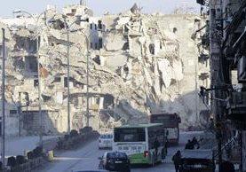 Varios vehículos pasan frente a edificios destruidos en el barrio de al-Shaar, Alepo.(AFP).