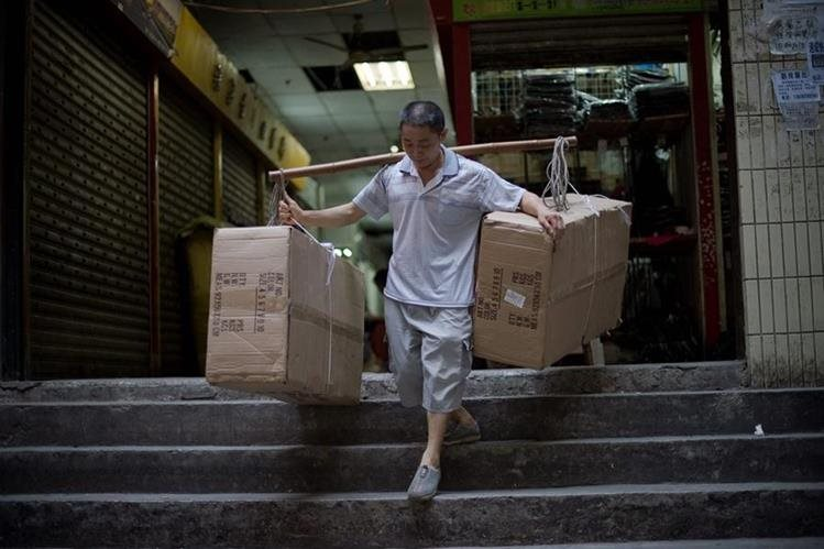 Con varas de bambú los porteadores cargan los objetos más pesados (Foto Prensa Libre: AFP)