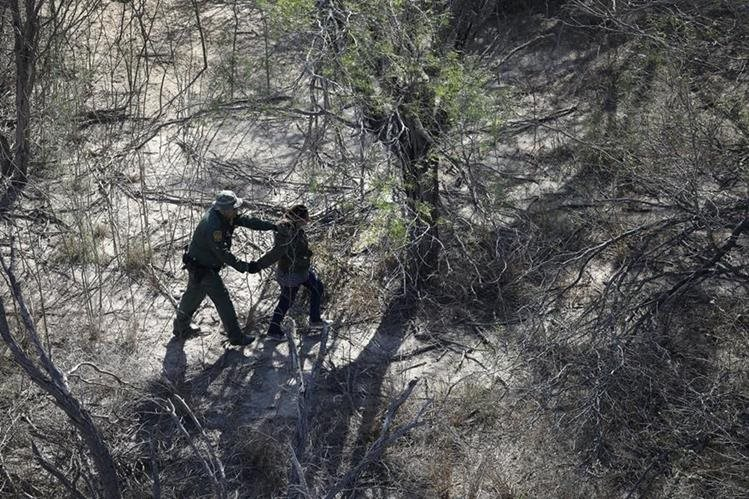 Un agente de la patrulla fronteriza de los EE. UU. detiene a un inmigrante indocumentado cerca de la frontera EE. UU.-México.(Foto Prensa Libre: AFP).
