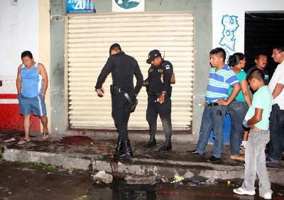 Agentes de la policía y curiosos observan la escena donde ocurrió el crímen. (Foto Prensa Libre: Rolando Miranda)