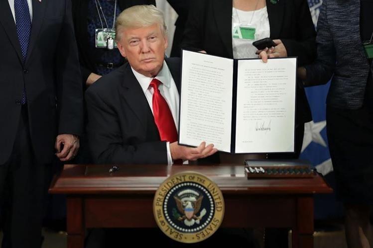 El presidente Donald Trump muestra la firma del aprobación del muro. (Foto Prensa Libre: EFE)