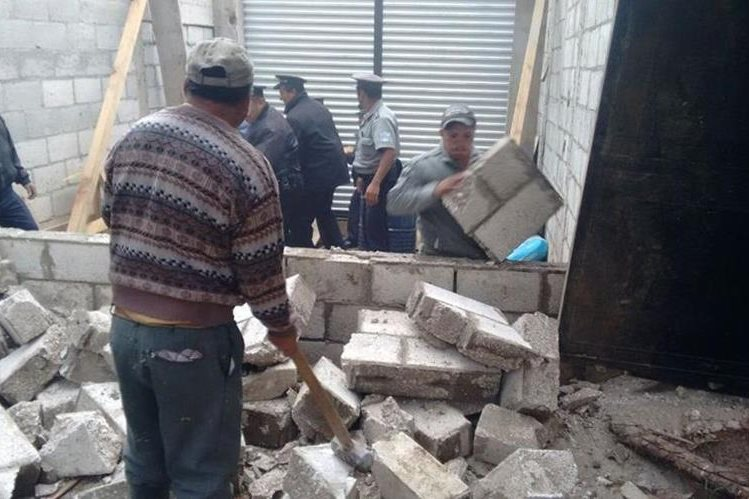 Policías ayudan a derribar pared de local, en Quetzaltenango. (Foto Prensa Libre: María José Longo).