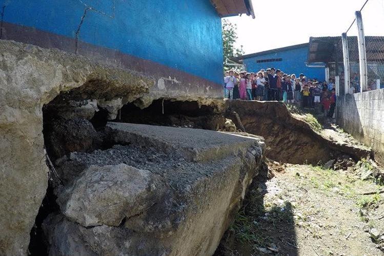 Niños observan el agujero que afecta a la escuela en San Pedro Carchá. (Foto Presa Libre: Eduardo Sam).