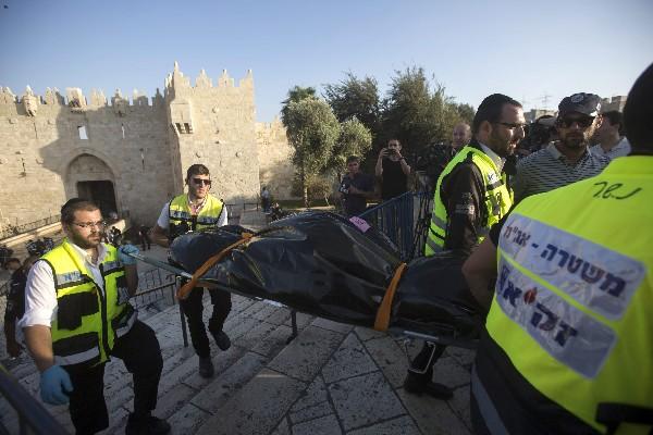 Personal de servicios de la unidad de rescate trasladan el cuerpo de un palestino asesinado en Jerusalén.