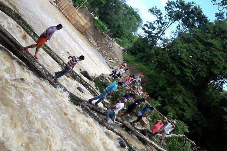 Personas usan ramas para cruzar el río Jubuco en aldea Natalia, Los Amates, izabal. (Foto Prensa Libre: Dony Stewart)