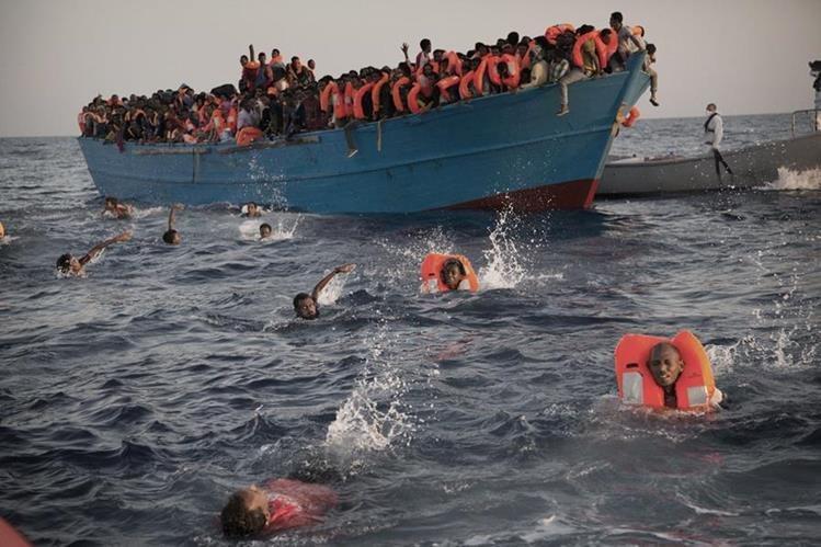 Migrantes desesperados se lanzan de bote a punto de zozobrar, en costa libia. (Foto Prensa Libre: AP)