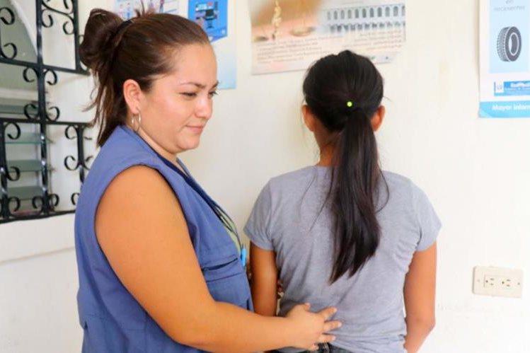 Una delegada de la PGN junto con la pequeña de 12 años que sufría agresión. (Foto Prensa Libre: Rolando Miranda)
