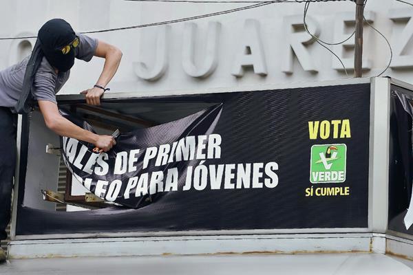 Un manifestante destroza una bandera electoral del Partido Verde durante una protesta en la ciudad de México. (Foto Prensa Libre:AFP).
