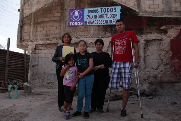 Miembros de la familia Castillo posan en  el terreno donde estaba su vivienda, la cual se destruyó por el terremoto.