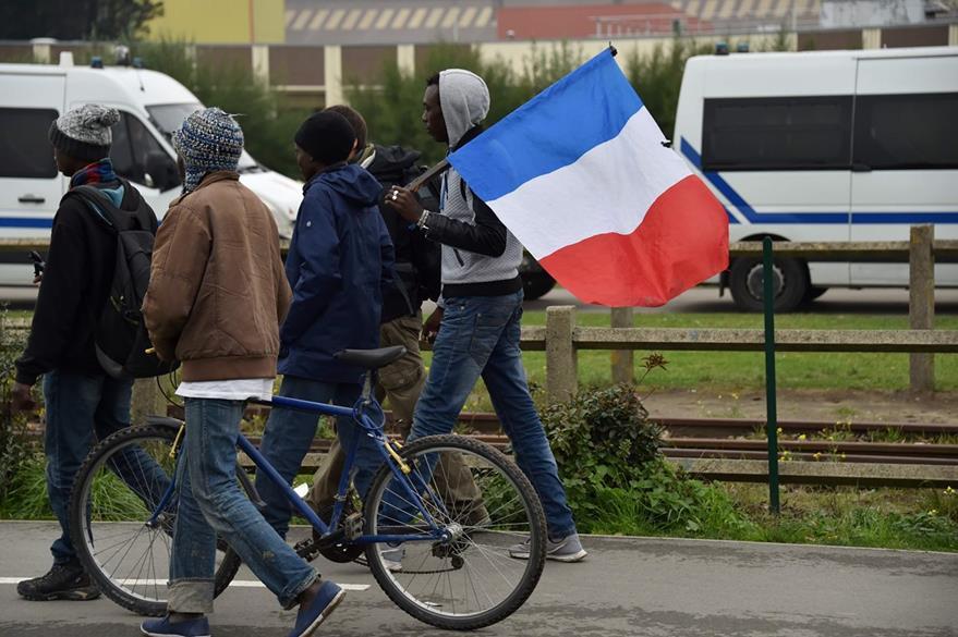 Un migrante abandona Calais llevando consigo una bandera francesa. (Foto Prensa Libre: AFP).