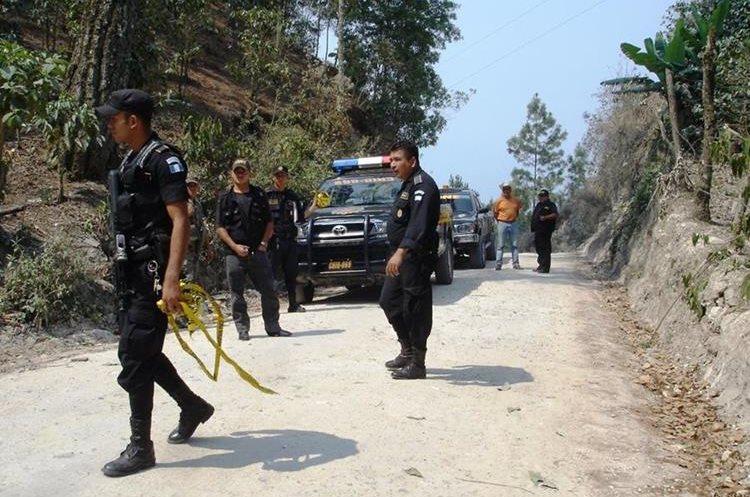 Agentes de la PNC resguardan la escena del crimen mientras peritos del MP recaban evidencias. (Foto Prensa Libre: Mario Morales)