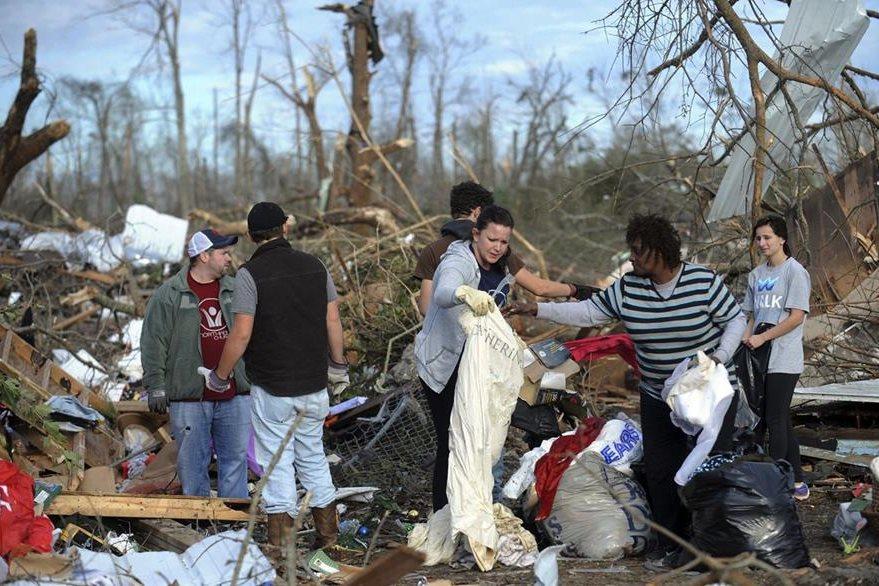 Varias personas rescatan pertenencias en Mississippi luego del tornado. (Foto Prensa Libre: AP).