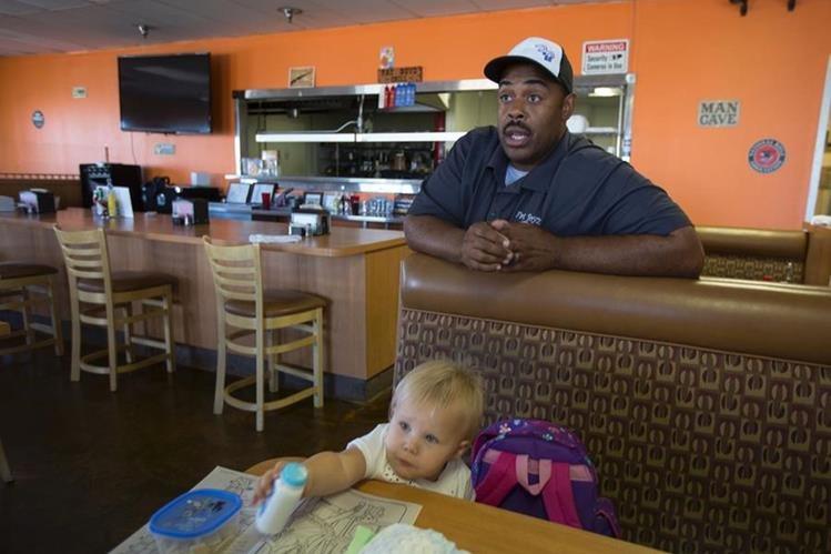 """Jermaine Wright habla con un reportero dentro de su restaurante, cerca de la """"zona verde"""", área designada por la ciudad para el desarrollo del cultivo de la marihuana a escala industrial en Adelanto, California. (Foto Prensa Libre: AFP)."""