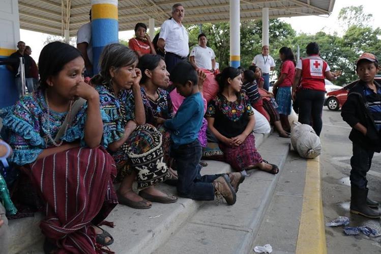 Mujeres y niños, junto a costales donde guardan ropa, esperan en la frontera de Corinto, entre Honduras y Guatemala, luego de que fueran víctimas de trata de personas y explotación laboral en aquel país. (Foto Prensa Libre: Dony Stewart)