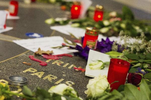 Flores, mensajes y velas dejados en una zona peatonal en memoria de las víctimas de los atentados de París.