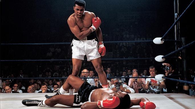 """Una de las fotos más icónicas de Muhammad Alí, cuando noquea a Sonny Liston en el pimer round. Su rival de pondría de pie solo para que la pelea terminara unos segundos después. El gran momento fue captado por el fotógrafo Neil Leifer para la revista """"Sports Illustrated"""" en mayo de 1965. (Foto: Infobae)."""