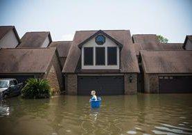 Jenna Fountain lleva un cubo para intentar recuperar los artículos de su hogar inundado Port Arthur, Texas. Los residentes de Houston y otras ciudades de Texas comenzaron a regresar a casa para evaluar los daños causados por el huracán Harvey.(Foto, Prensa Libre: AFP)