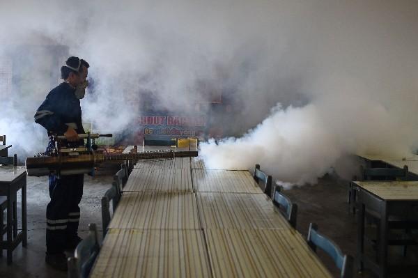 Un trabajador fumiga en un sector afectado por el mosquito transmisor del zika. (AFP).