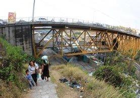 Las familias entran y salen del barrio a cualquier hora del día y retan el ruido, la vibración y la amenaza de la gigantesca estructura del puente Belice. (Foto Prensa Libre: Esbin García)