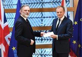 Embajador británico Tim Barrow entrega la carga que oficializa la salida del Reino Unido de la Unión Europea al presidente del concejo Donald Tusk. (Foto Prensa Libre: AFP)