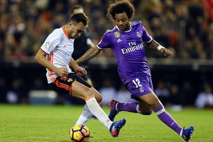 El delantero del Valencia Munir El Haddadi (i) disputa un balón con el defensa brasileño del Real Madrid Marcelo. (Foto Prensa Libre: EFE)