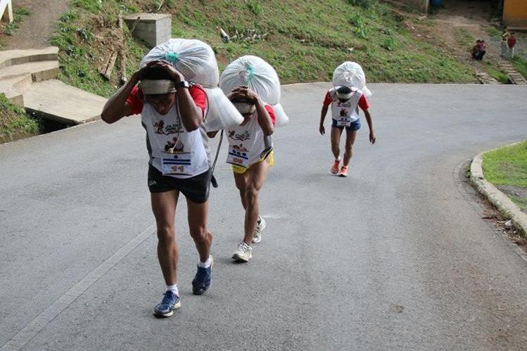Tres participantes de la carrera de los Hombres de Maíz se esfuerzan por llegar a la meta, en Tactic, Alta Verapaz. (Foto Prensa Libre: Eduardo Sam Chun)