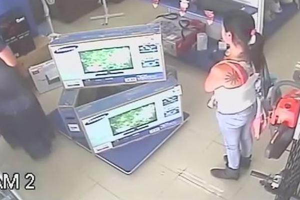 La mujer de vestido azul se apresta a robar el televisor. Su acompañante se mantiene atenta.