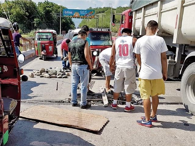 Un grupo de pilotos de El Rancho repara el puente Chetumal.