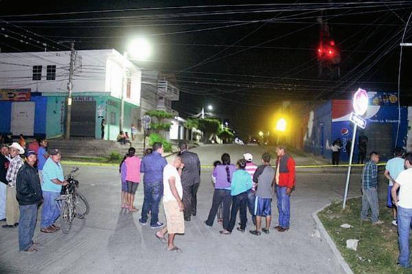 Vecinos observan el trabajo de la Policía Nacional Civil que recoge evidencias del ataque armado. (Foto Prensa Libre: Hugo Oliva).
