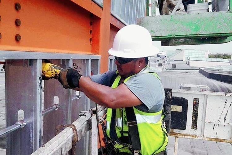 Marco Antonio Rivera Sitalán, de Retalhuleu, coloca una estructura metálica en un edificio, en Palm Beach, Florida, Estados Unidos, a donde emigró de manera ilegal.