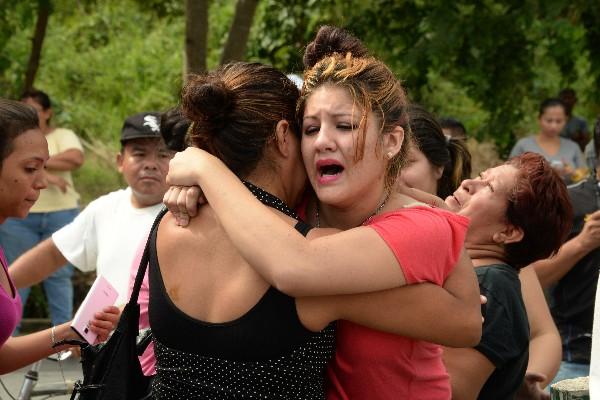 Familiares de las vítimas se consuelan en la escena del crimen en la estación de autobuses en Choloma,Honduras.