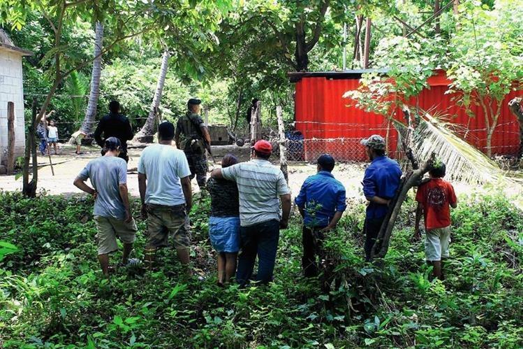 Curiosos permanecen en el lugar donde murió baleada Marta Elena Contreras, en Masagua, Escuintla. (Foto Prensa Libre: Enrique Paredes)
