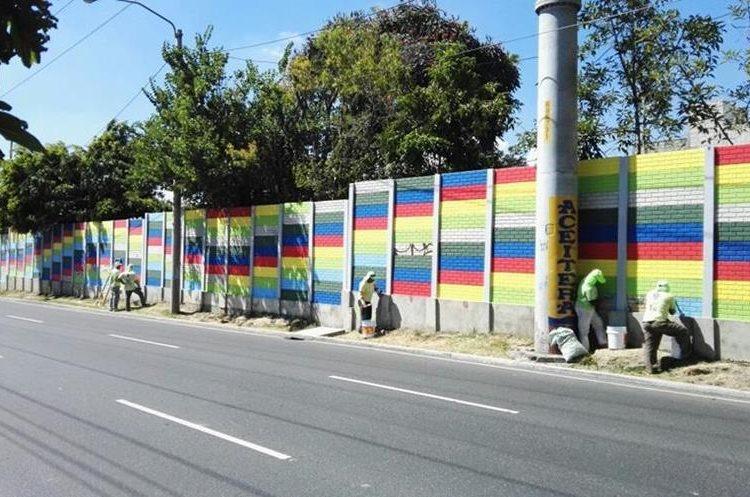 En la 47 calle de la calzada Atanasio Tzul, colaboradores de la comuna capitalina pintan un mural con arte cinético. (Foto Prensa Libre: Edwin Pitán)