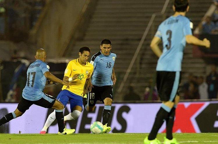 Neymar conduce la pelota en medio de los rivales de Uruguay.