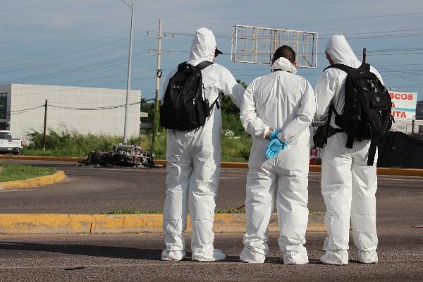 Un grupo de forenses observan la escena del crimen en Culiacán, Sinaloa, México.(AFP).