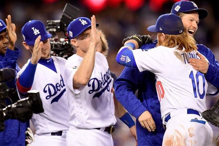 Clayton Kershaw celebra con Justin Turner #10 el primer triunfo de los Dodgers en la Serie Mundial. (Foto Prensa Libre: AFP)