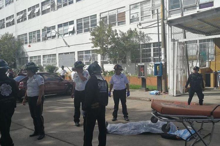 Dos cuerpos quedaron tendidos afuera de la emergencia del hospital, frente a la farmacia. (Foto Prensa Libre: Estuardo Paredes)