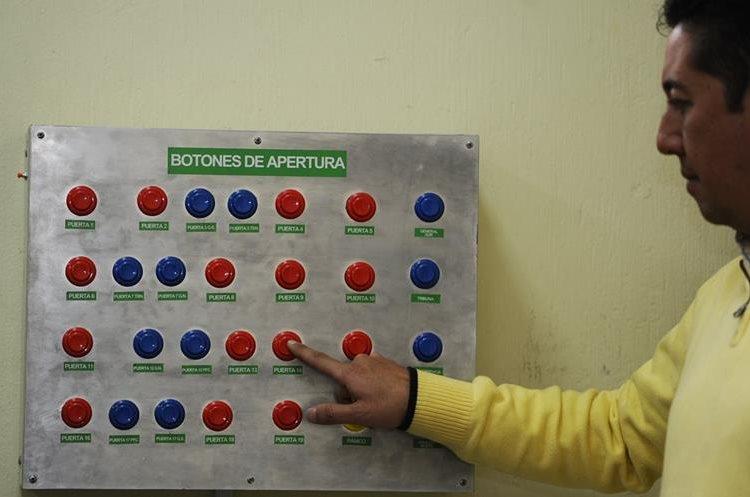 Carlos López, de la CDAG, muestra el tablero de botones que controla las 19 puertas de emergencia colocadas en el Mateo Flores. (Foto Prensa Libre: Francisco Sánchez)