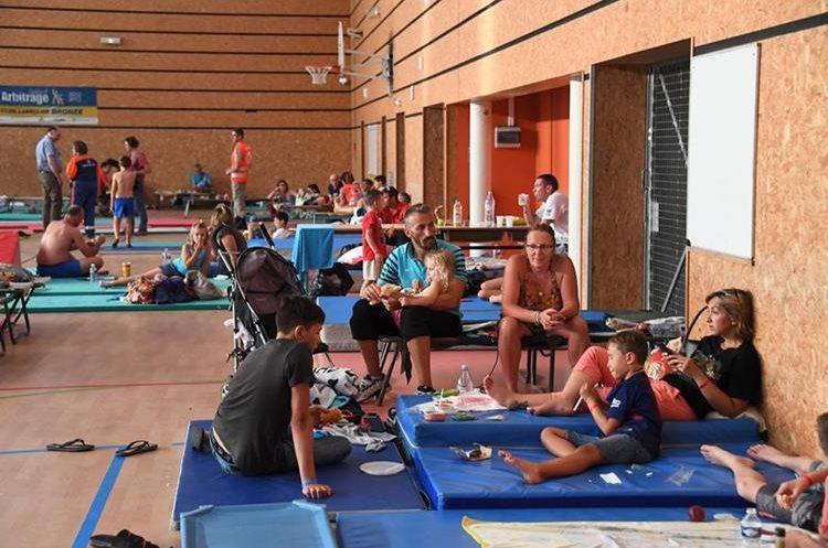 Varias personas se reúne en un gimnasio en después de ser evacuados. (AFP).