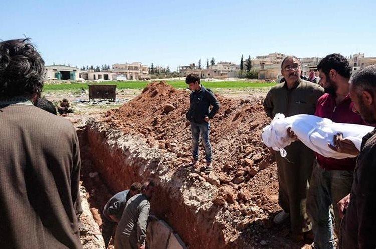 Un hombre sirio carga en brazos a un familiar víctima del ataque con gas sarín.