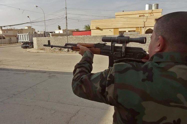 Un oficial del Ejército iraquí apunta con su arma un objetivo yihadista durante el ataque a Kirkuk. (Foto Prensa Libre: AFP).