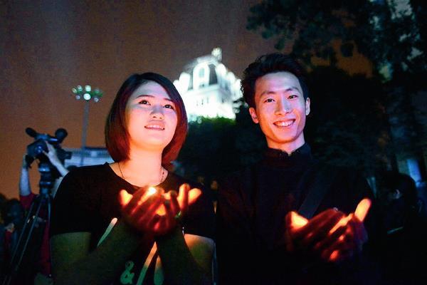 """Dos participantes se encienden velas durante la campaña la """"Hora del Planeta"""", en Hanoi, Vietnam. (Foto Prensa Libre:EFE)"""