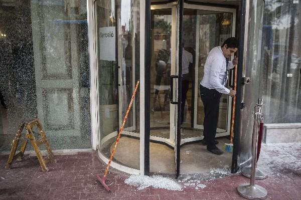 Un empleado del hotel limpia los cristales rotos después del ataque. (Foto Prensa Libre:AFP).